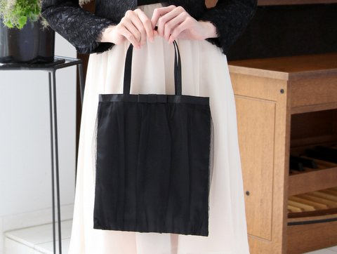 明るいカラーのドレスに映えるブラックのサブバッグ