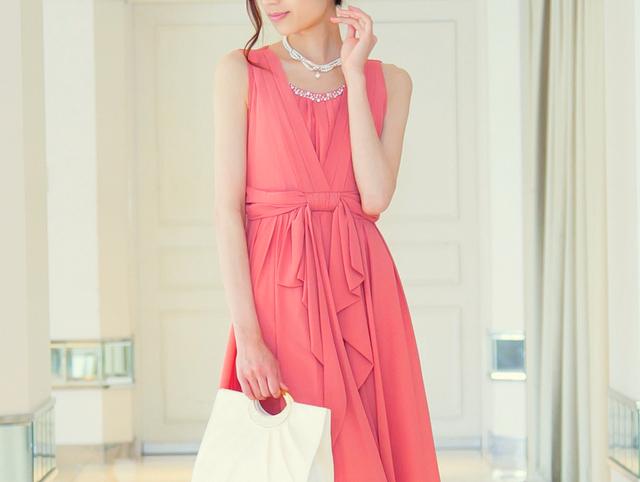 お腹まわりをカバーしながらスタイルアップも期待できるコーラルピンクのドレス